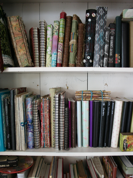 Bookshelf of journals and sketchbooks